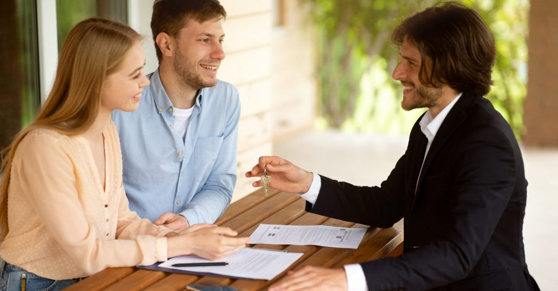 Real estate broker giving house key to millennial couple after signing property agreement at table outside, panorama